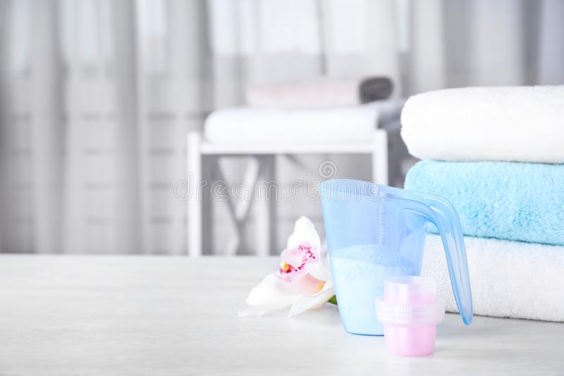 With clean towels and laundry detergents on table against blurred background. Space for text. Composition with clean towels and laundry detergents on table royalty free stock photo