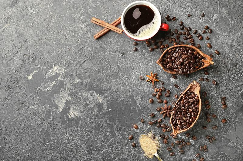 Composition with coffee beans and hot drink on grey table stock image