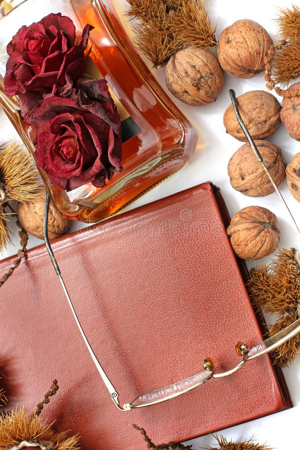 Composition. Cognac, a closed book, glasses and chestnuts stock image