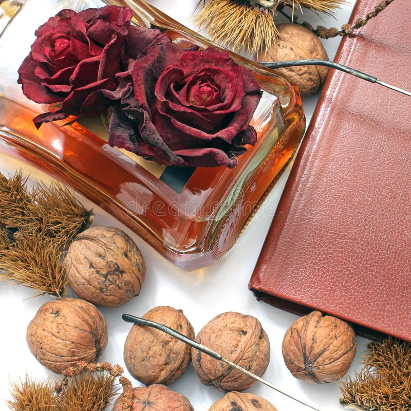 Composition. Cognac, a closed book, glasses and chestnuts stock photos