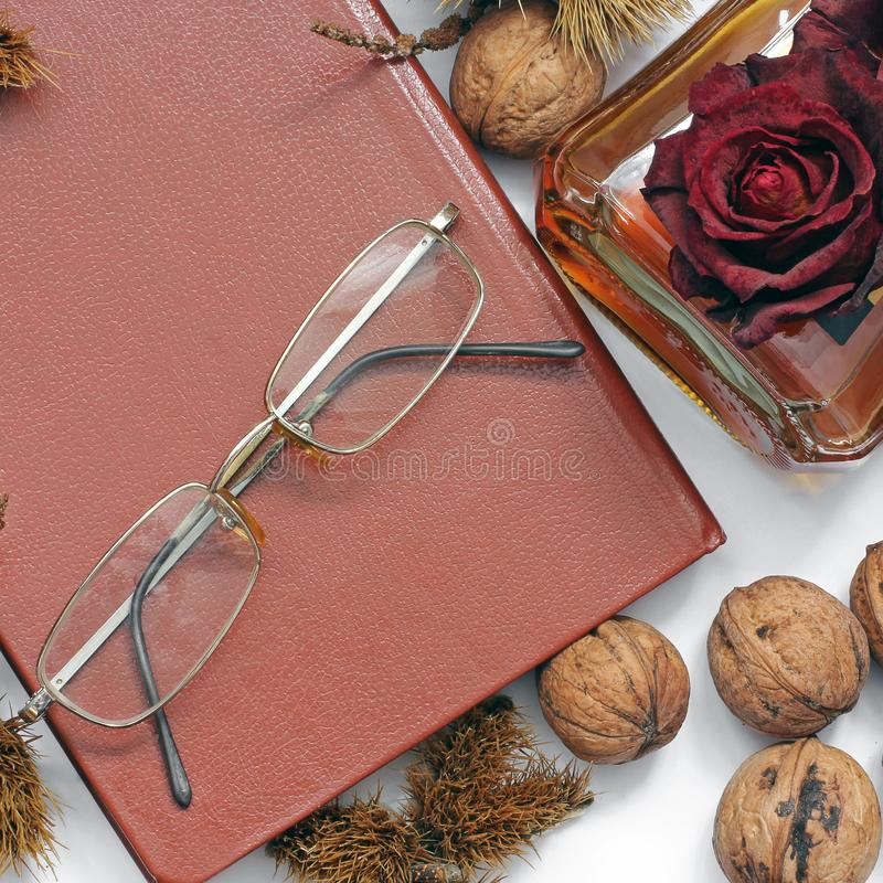 Composition. Cognac, a closed book, glasses and chestnuts stock photo