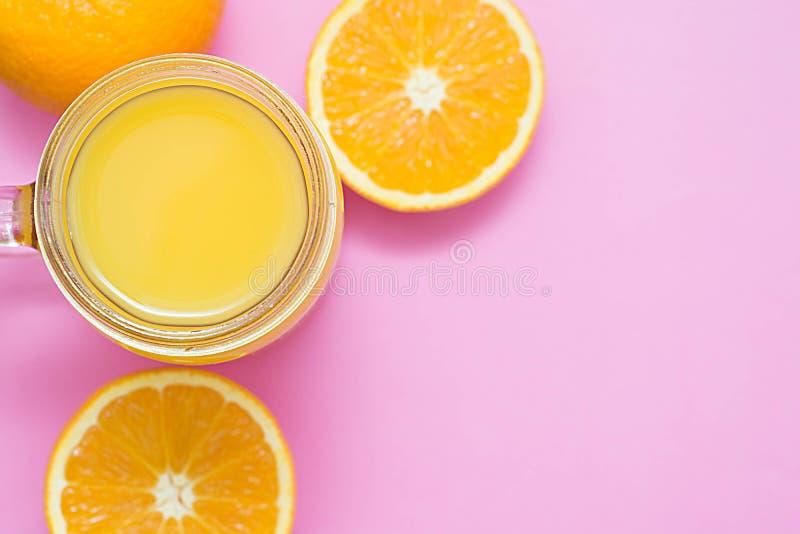 Composition colorée avec le verre de pot de maçon plein du jus d'orange frais avec la paille, fruit, d'isolement sur le fond rose images stock