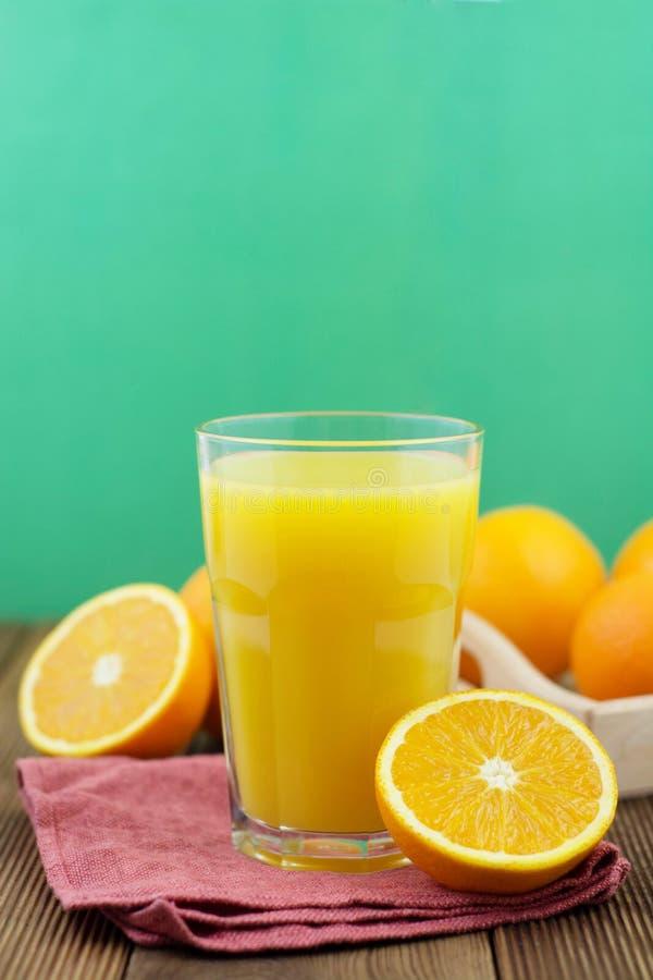 Composition colorée avec le verre de pot de maçon plein du jus d'orange frais avec la paille, fruit, d'isolement sur le fond vert photographie stock