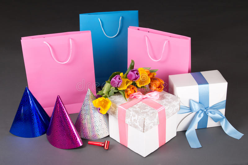 Composition of colorful tulips, gift boxes and birtday hats. Composition of colorful flowers, gift boxes and birtday hats royalty free stock photo