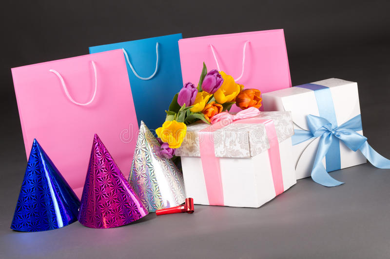 Composition of colorful tulips, gift boxes and birtday hats over. Composition of colorful flowers, gift boxes and birtday hats over grey royalty free stock images