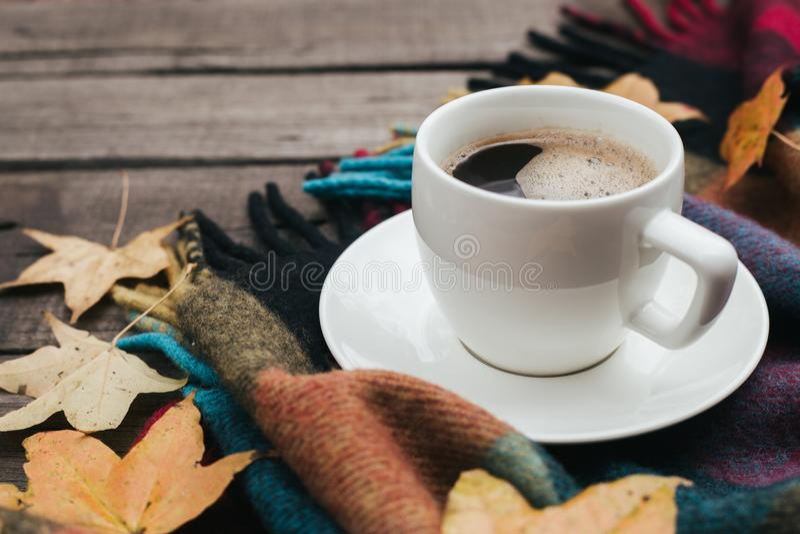 Composition confortable en automne avec des feuilles de plaid et une tasse de café sur le fond en bois de vieux vintage images stock