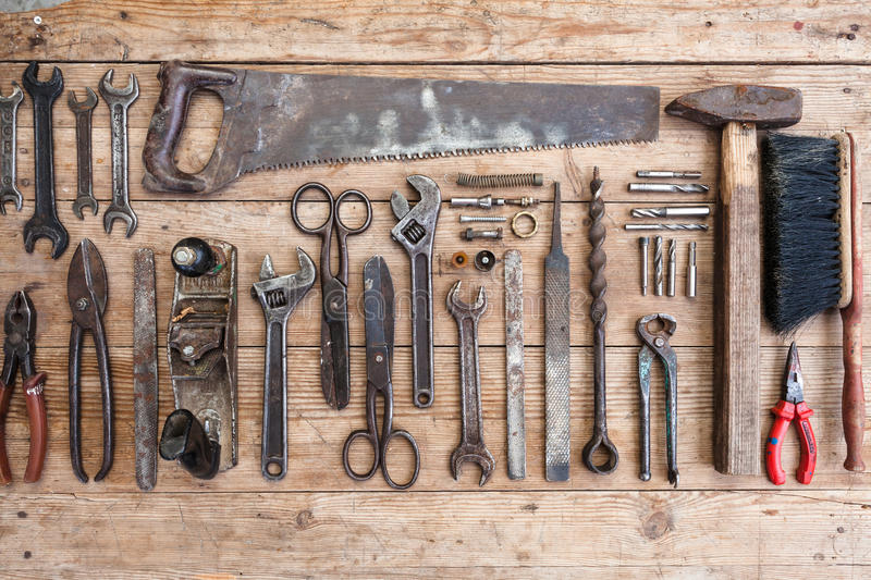 Composition of construction tools on an old battered wooden surface of tools: pliers, pipe wrench, screwdriver, hammer, metal shea royalty free stock photography