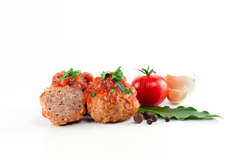 Composition with cooked meatballs with tomato sauce on the white stock images