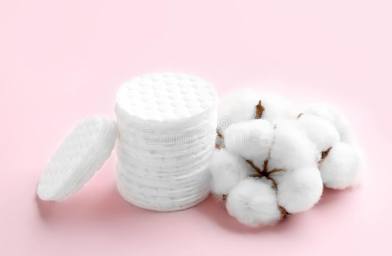 Composition with cotton pads and flowers. On color background stock photography