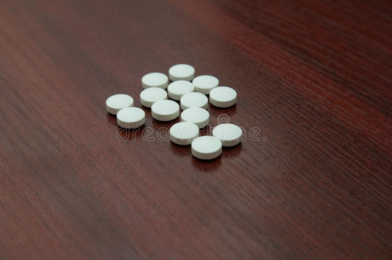 White pills. Composition by CU from large white pills spilled on a table stock photography