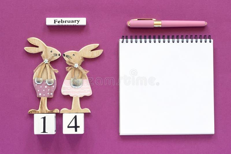 Composition cubes calendrier paires romantiques du 14 février de lapins en bois de figurine d'amants, carnet vide ouvert pour le  photos stock