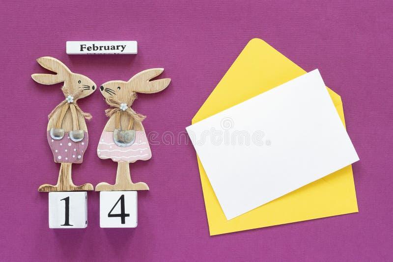 Composition cubes calendrier paires romantiques du 14 février de lapins en bois de figurine d'amants, enveloppe jaune avec la car photographie stock libre de droits