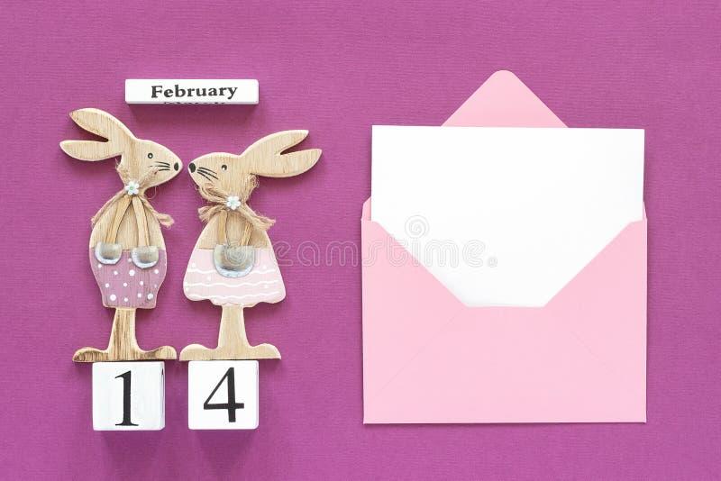 Composition cubes calendrier paires romantiques du 14 février de lapins en bois de figurine d'amants, enveloppe rose avec la cart photo stock
