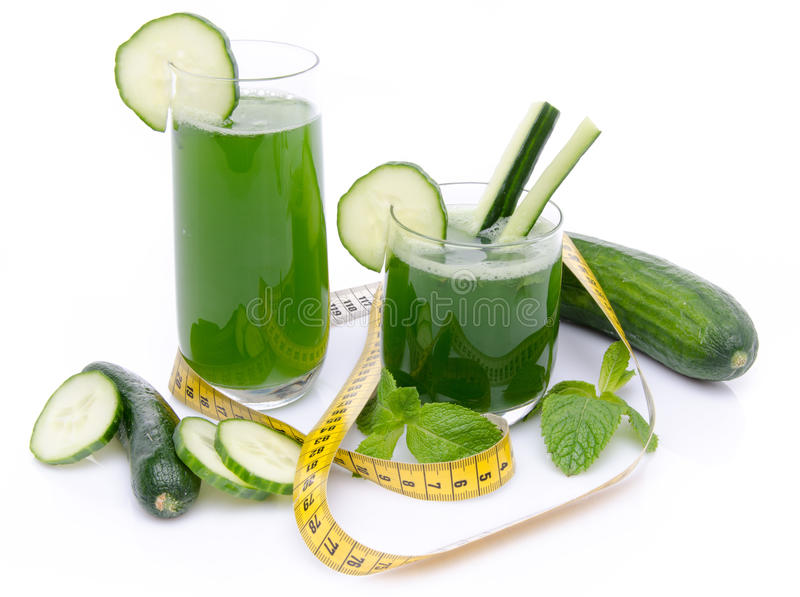 Composition with cucumber juice, fresh cucumbers and a tape meas. Ure, isolated on white royalty free stock photography