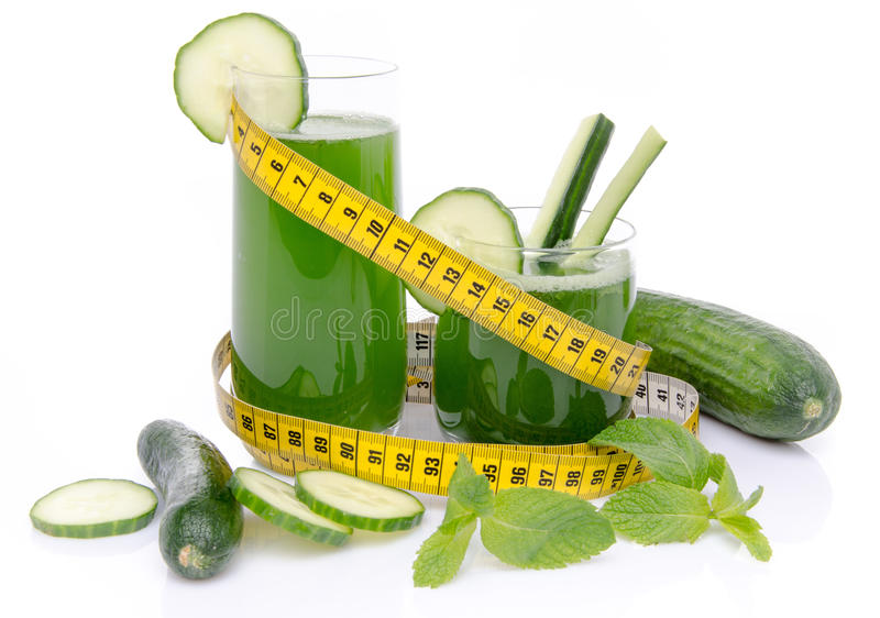 Composition with cucumber juice, fresh cucumbers and a tape meas. Ure, isolated on white royalty free stock photo