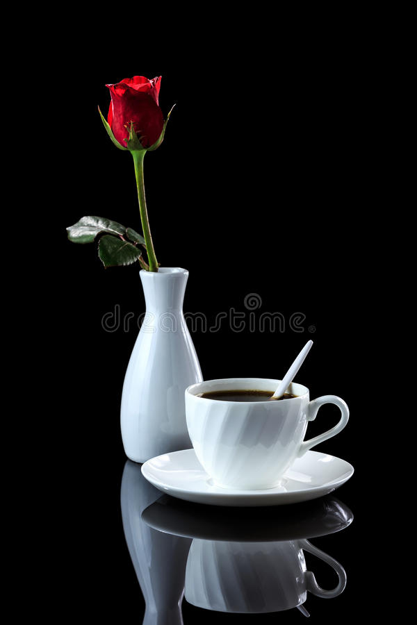 Composition with cup of coffee and rose on a black reflective bac. Kground with backlight. Studio shot stock photos