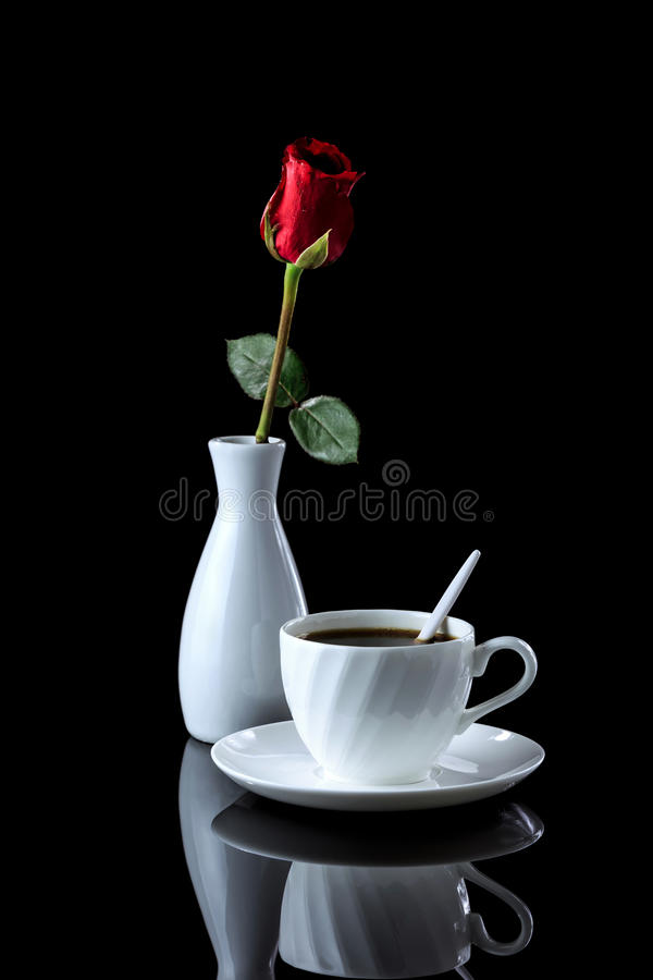 Composition with cup of coffee and rose on a black reflective bac. Kground. Studio shot stock photos