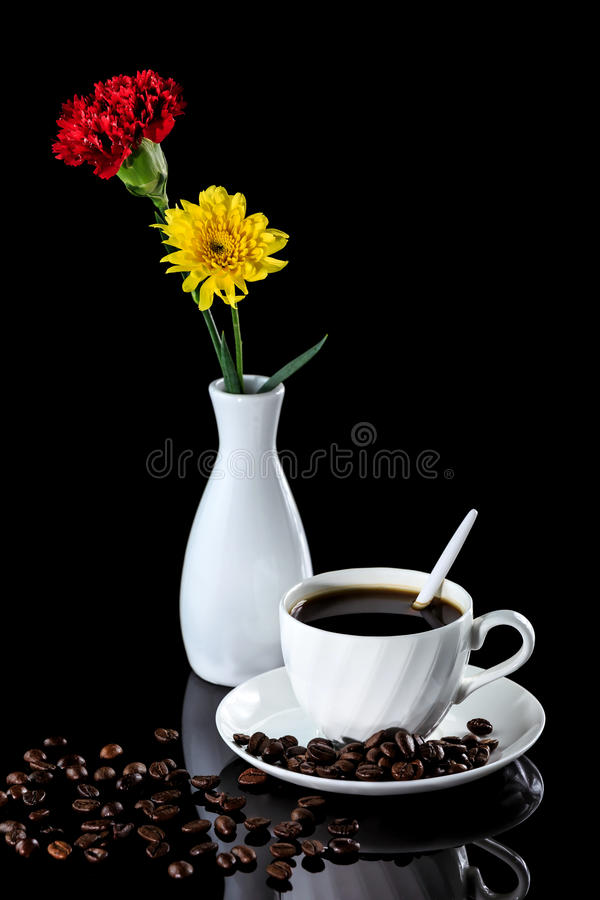 Composition with cup of coffee , yellow chrysanthemum and carnatio. N on a black reflective background. Studio shot stock photography