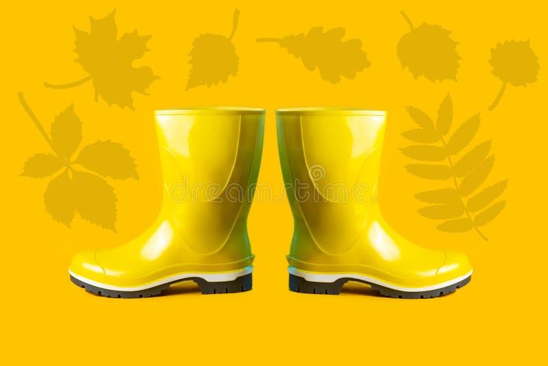 Composition d'automne des bottes en caoutchouc et des feuilles jaunes image libre de droits