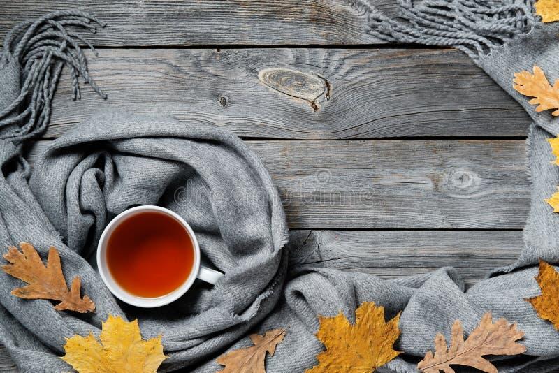 Composition d'automne, feuilles de chute, tasse de cuisson à la vapeur chaude de thé et une écharpe chaude sur le fond en bois de images stock