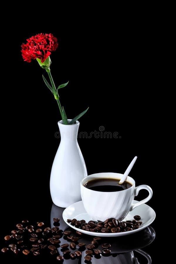 Composition de café et d'oeillet rouge sur un Ba réfléchi noir photos stock
