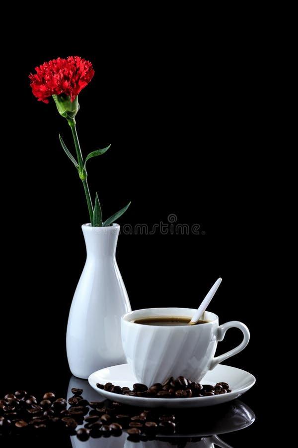 Composition de café et d'oeillet rouge sur un Ba réfléchi noir photos libres de droits