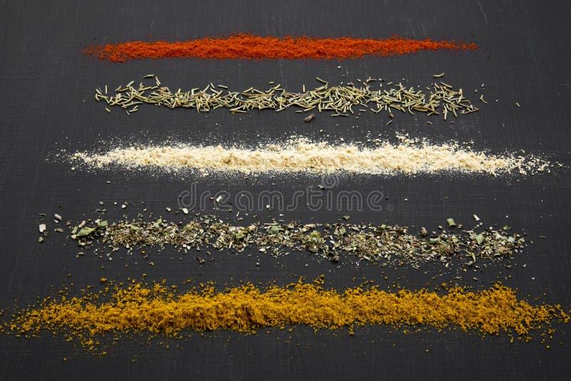 Composition de différentes épices et herbes au-dessus de fond noir, image stock