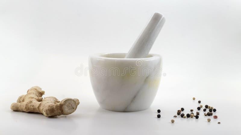 Composition de marbre en mortier avec le poivre de racine de gingembre et blanc, rouge et noir sur un fond blanc photo stock