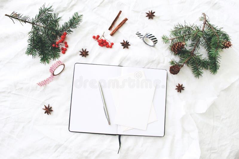 Composition de Noël Bloc-notes vide, scène de maquette de cartes de voeux Branches d'arbre de Noël, baies de sorbe rouges, pin photographie stock libre de droits
