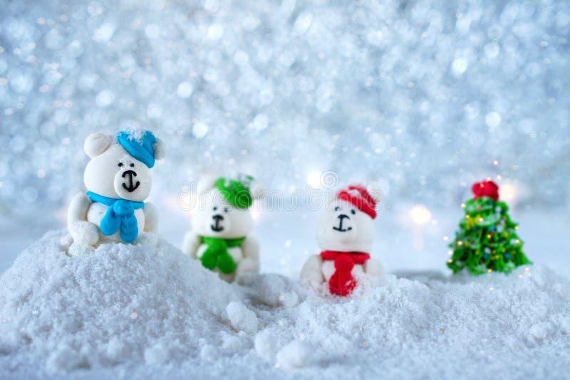 Composition de Noël La nouvelle année joue - trois ours de sucrerie de sucre jouant dans la neige sur le fond de bokeh photo libre de droits