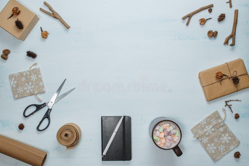 Composition de Noël Le cadeau de Noël, les ciseaux, carnet avec le stylo, cacao avec la guimauve, cadeau met en sac, des cônes de images libres de droits
