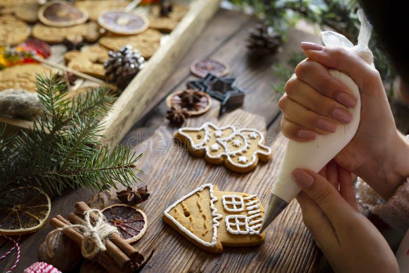 Composition de Noël Les mains des femmes garnissent du pain d'épices avec glaçage photos libres de droits