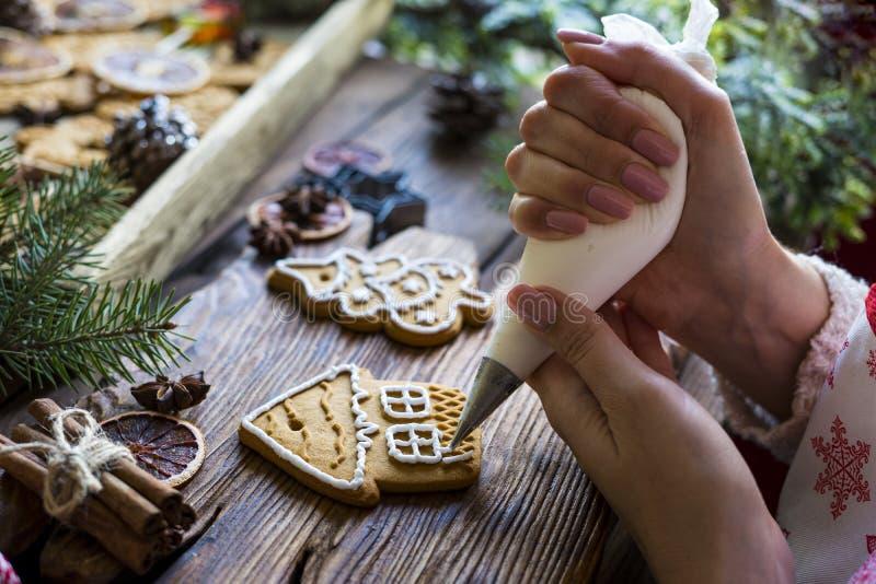 Composition de Noël Les mains des femmes garnissent du pain d'épices avec glaçage photographie stock