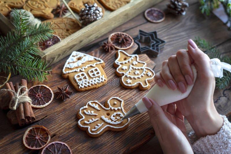Composition de Noël Les mains des femmes garnissent du pain d'épices avec glaçage photo stock