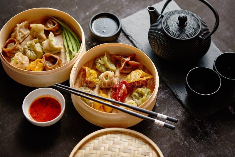 Composition de nourriture chinoise Genres mélangés de boulettes de vapeur en bambou en bois photo stock