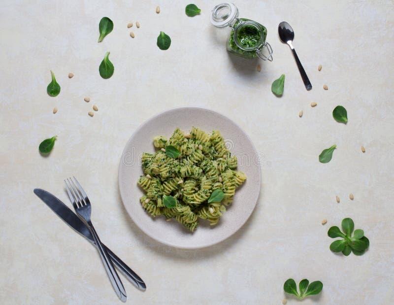 Composition de plat avec des pâtes en sauce à pesto, vert de feuille, pignons sur le fond clair photographie stock