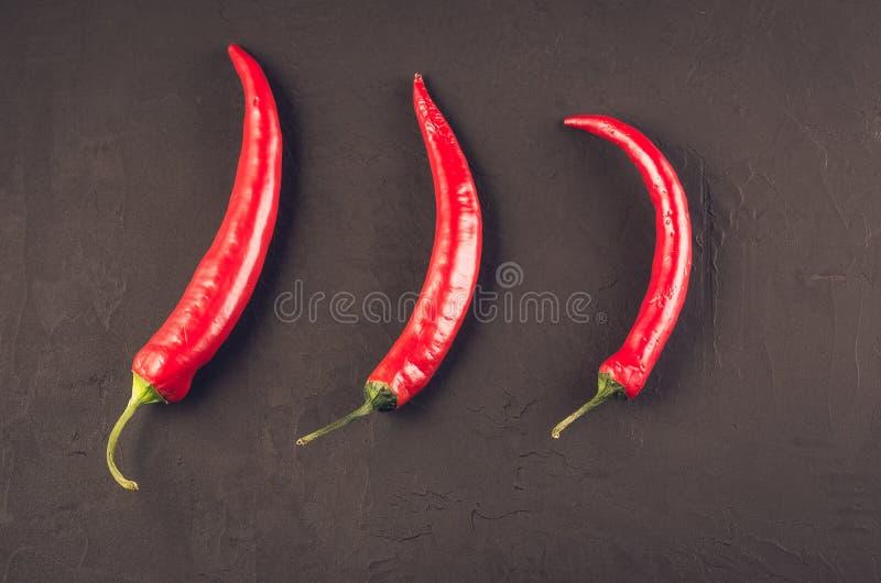 Composition de poivre de piment/de poivre d'un rouge ardent du Chili sur un fond en pierre fonc? Vue sup?rieure image stock