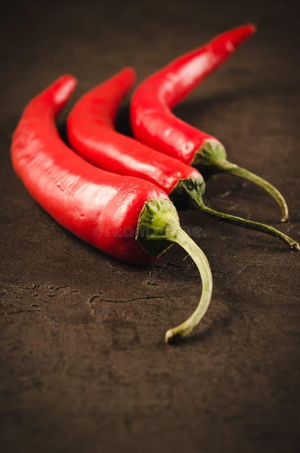 Composition de poivre de piment/de poivre d'un rouge ardent du Chili sur une pierre foncée images libres de droits