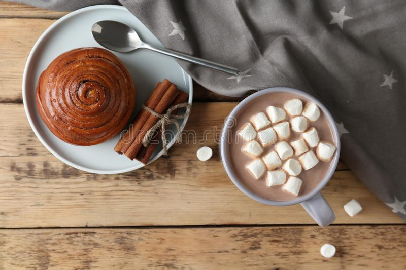 Composition with delicious hot cocoa drink and bun on background, flat lay. Composition with delicious hot cocoa drink and bun on wooden background, flat lay stock photo