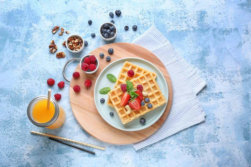 Composition with delicious waffles and berries on color background royalty free stock images