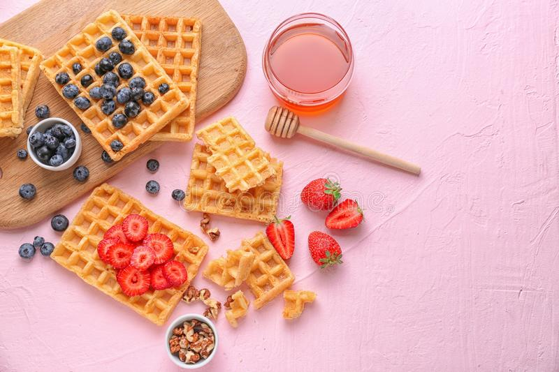 Composition with delicious waffles and berries on color background stock photography