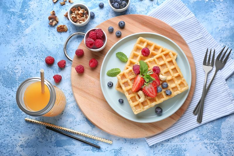 Composition with delicious waffles and berries on color background stock photos