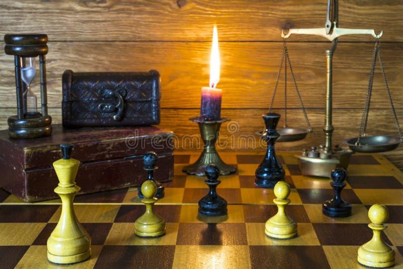 Composition des chiffres d'échecs, des sable-verres, de vieux tronc et des échelles en bronze photo stock