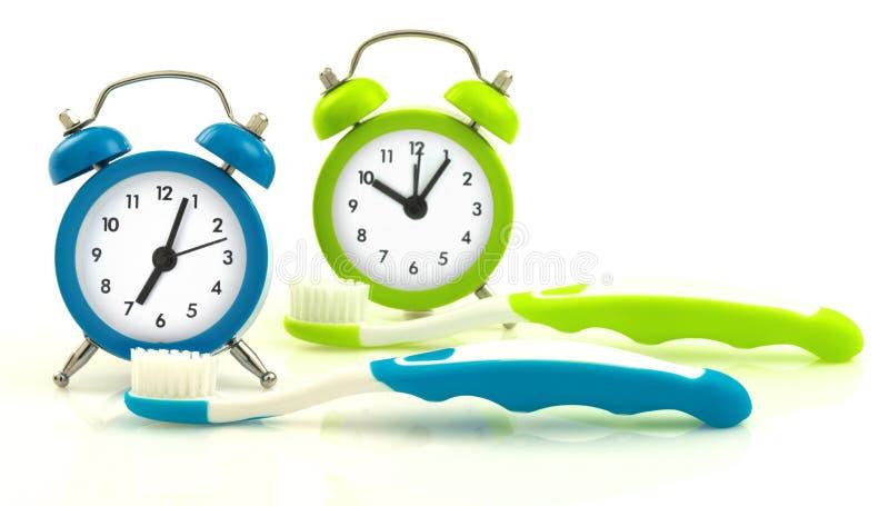Composition des horloges et des brosses à dents bleues et vertes image libre de droits
