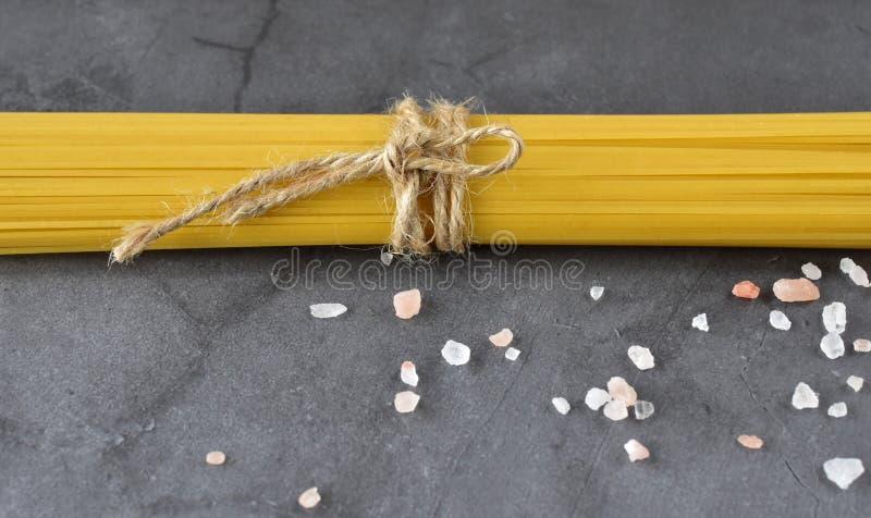 Composition des spaghetti attachés avec la ficelle et le sel rose de mer sur un fond gris images libres de droits