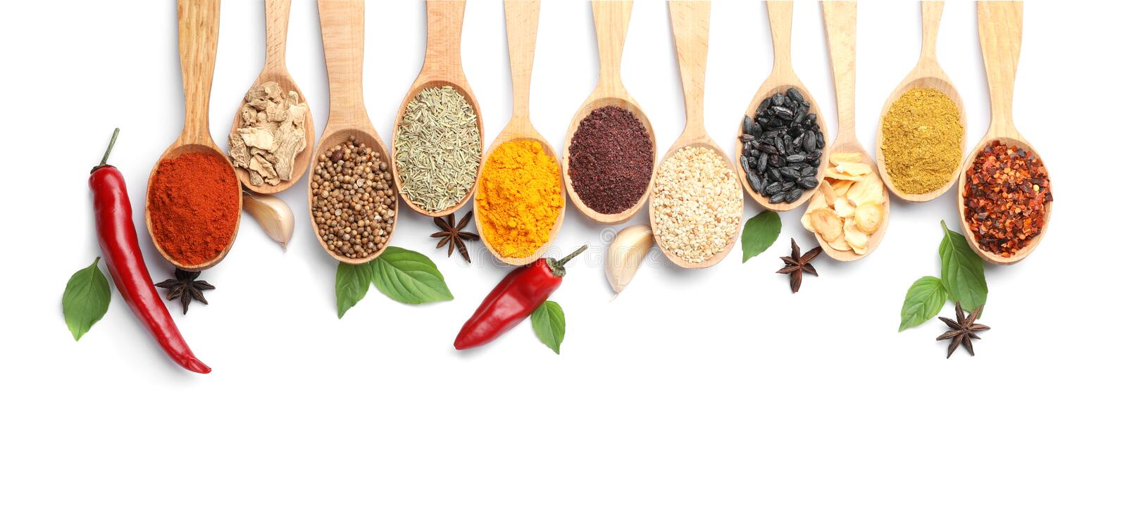 Composition with different aromatic spices in wooden spoons stock images