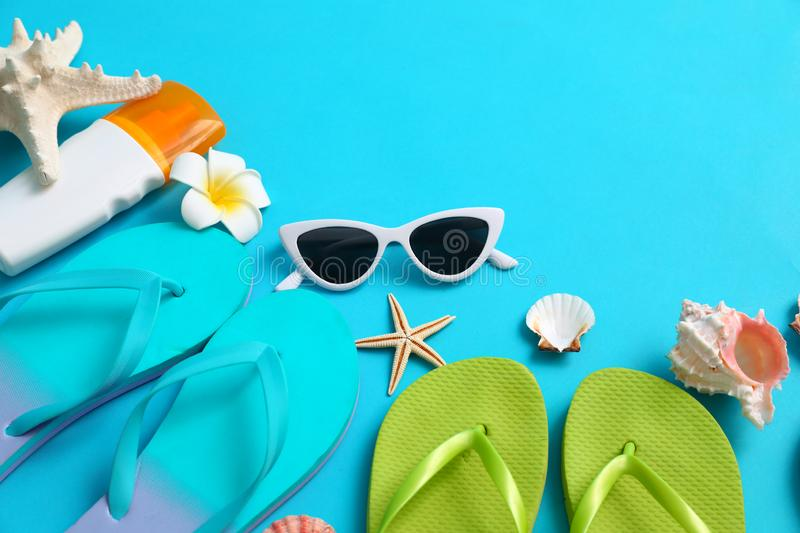Composition with different flip flops on blue , space for text. Summer beach accessories. Composition with different flip flops on blue background, space for royalty free stock photo