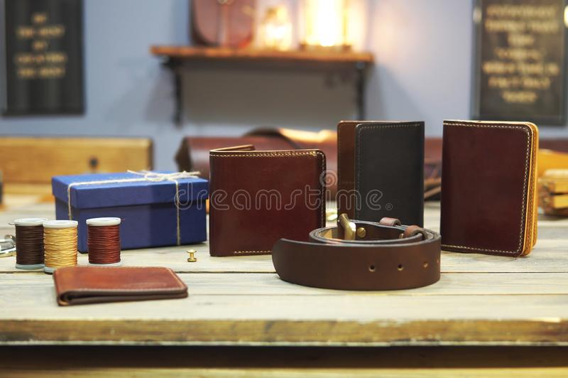 Composition of different hand made leather man accessories on wooden background. Wallet, belt, purse, gift box, thread. On wooden table stock photography