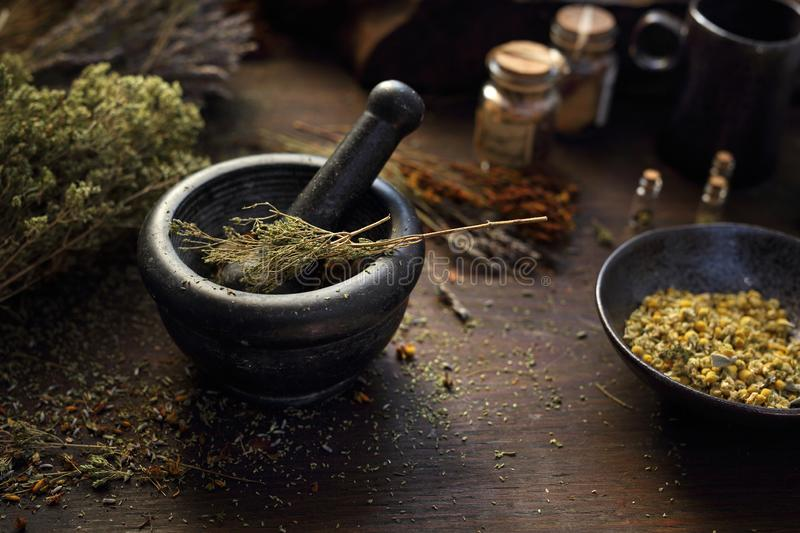 Composition of dried herbs. Aromatic mixture grated in mortar. A composition of herbs, flowers and spices. Healthful potions and infusions on a wooden table stock photography