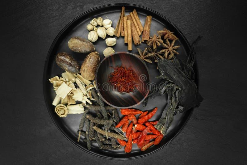 Composition du mélange de diverses épices sèches exotiques dans la cuvette ronde noire sur le fond en pierre noir images libres de droits